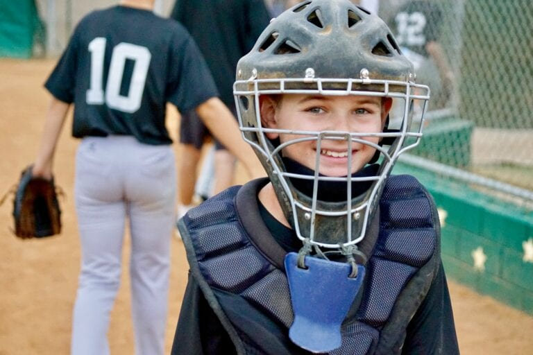 An amazing, happy and awesome kid, smiling after a baseball game, well played
